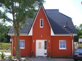 Фасад дома выкрашен в насыщенный кирпичный цвет, крыша выложена серой черепицей.  Дом красного цвета.